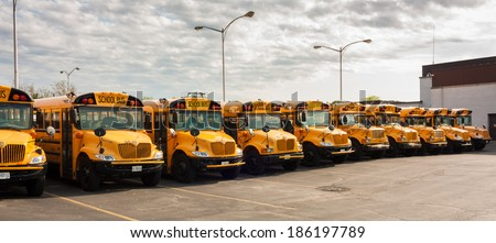 CHICAGO - MAY 25, 2012: Yellow school buses parked in line at their depot. Each school day in 2012 approximately 468,000 school buses transport 28.8 million children to and from school and activities. - stock photo