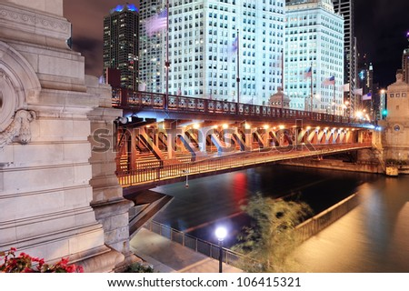 Chicago River Walk with urban skyscrapers and bridge illuminated with lights and water reflection at night. - stock photo