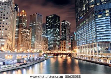Chicago River Walk with urban skyscrapers illuminated with lights and water reflection at night. - stock photo