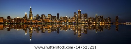 Chicago Skyline panorama mirrored view in water over Lake Michigan at dusk  - stock photo