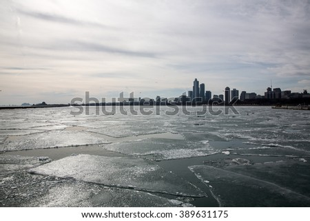Chicago skyline seen over Lake Michigan covered in broken ice on a sunny winter day. View from Chicago harbor. Illinois, USA. - stock photo