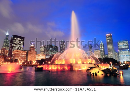 Chicago skyline with skyscrapers and Buckingham fountain in Grant Park at dusk lit by colorful lights. - stock photo
