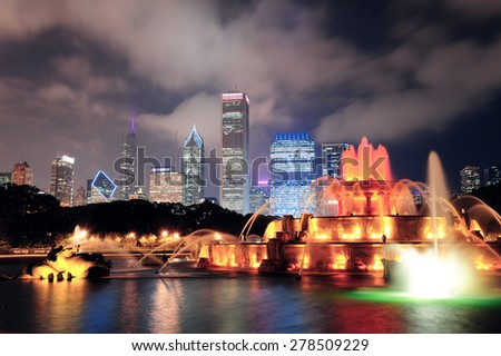 Chicago skyline with skyscrapers and Buckingham fountain in Grant Park at night lit by colorful lights. - stock photo