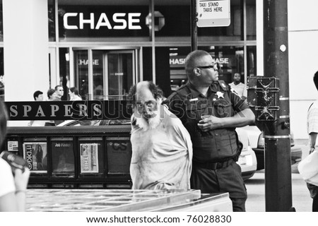 CHICAGO, USA - JUL 17: Policeman arrested a homeless man on Michigan Avenue in Downtown Chicago. July 17, 2010 in Chicago, USA.