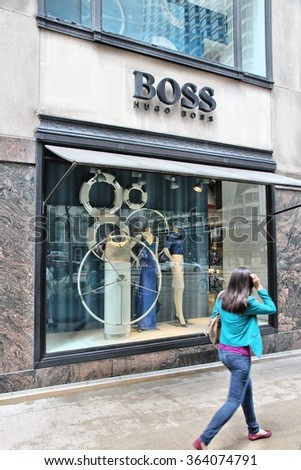 CHICAGO, USA - JUNE 26, 2013: Person walks by Hugo Boss store at Magnificent Mile in Chicago. The Magnificent Mile is one of most prestigious shopping districts in the United States. - stock photo