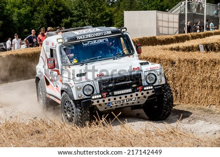Chichester, West Sussex, UK - June 29, 2014: Landrover rally vehicle slides around corner with hay bails separating onlookers from the course  - stock photo