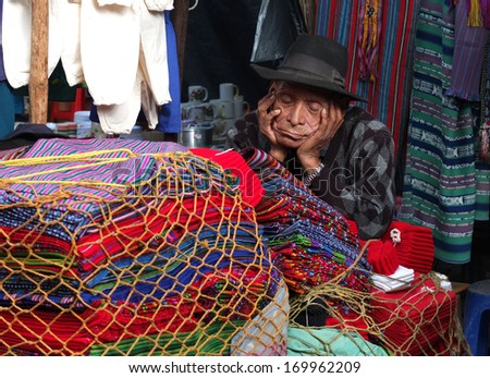CHICHICASTENANGO, GUATEMALA -  DECEMBER 1  A very old seller, wearing a dark hat, is sleeping in his open-air shop in the market,  on December 1, 2013, in Chichicastenango, Guatemala   - stock photo