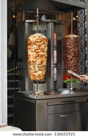 Chicken and beef meat on a vertical spit. A traditional food called Shawerma in Arabic and Doner in Turkish - stock photo