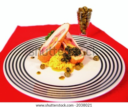 Chicken and ham cordon bleu style rolls on mashed potatoes and with capers - stock photo