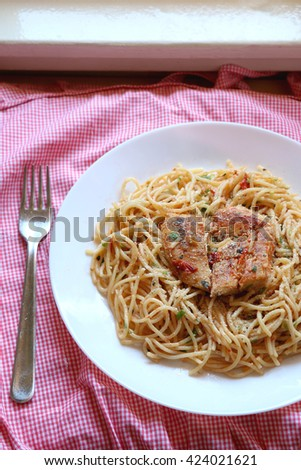 Chicken and pasta prepared with olive oil, tomatoes, parsley, garlic and butter. Checkered tablecloth, top view, selective focus. - stock photo
