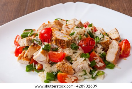 chicken and rice salad with fresh tomatoes in a plate on wooden table - stock photo