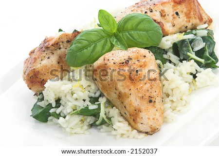 Chicken and rice with spinach and lemon toped with basil leaves - stock photo