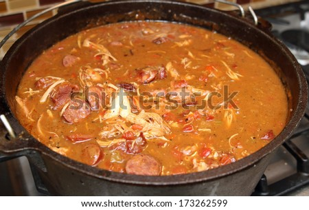 Chicken and sausage gumbo cooking in an iron kettle.