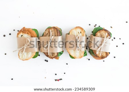 Chicken and spinach sandwiches wrapped in craft paper over a white wooden background with a copy space - stock photo