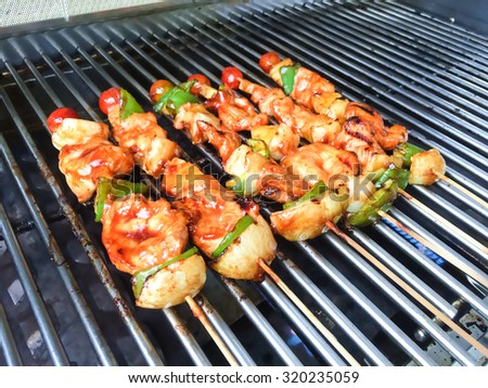 chicken barbecue kabobs on grill, background selection blurred - stock photo