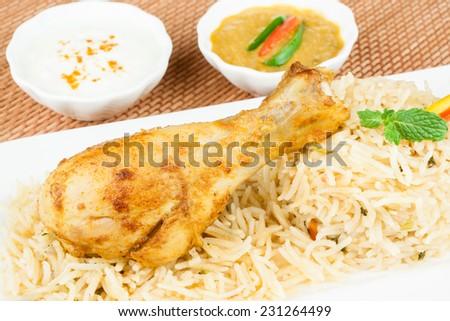 Chicken Biryani Closeup - Macro closeup view of delicious Indian chicken biryani with colorful garnish, served with raita and chicken gravy. Innovative presentation. - stock photo