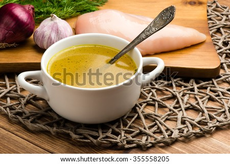 Chicken bouillon in the white bowl on the rustic wooden background. - stock photo
