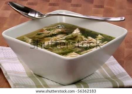 chicken breast and vegetables soup  made with low sodium  broth,  on fine wood table table. - stock photo
