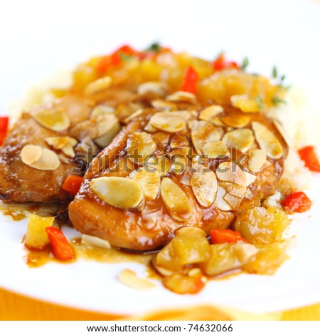 Chicken breast baked with almonds and apricot sauce on white plate, soft focus - stock photo