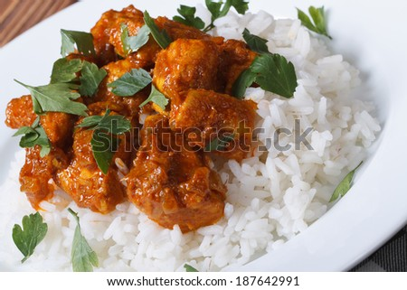 Chicken breast curry with rice on a white plate. Horizontal close-up   - stock photo