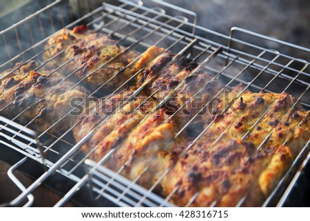 chicken breast grilled on a coals.