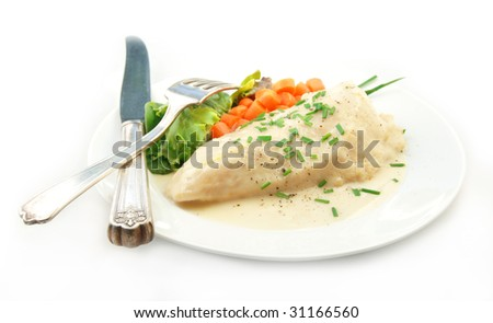 Chicken breast in a cream sauce with steamed vegetables on a white background.