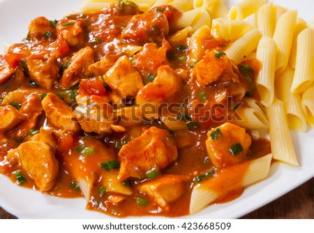 chicken breast in tomato sauce with penne pasta in a plate on wooden table - stock photo