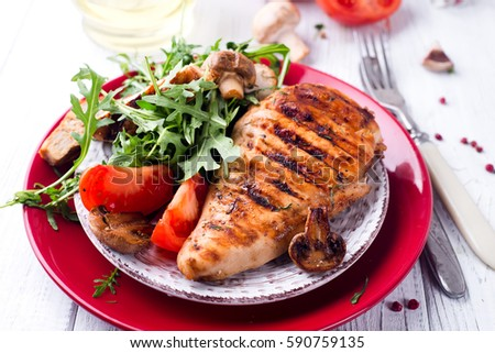 Chicken breast with fresh salad - arugula and tomato on a white wooden background