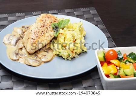 Chicken breast with smashed potatoes and vegetable salade - stock photo