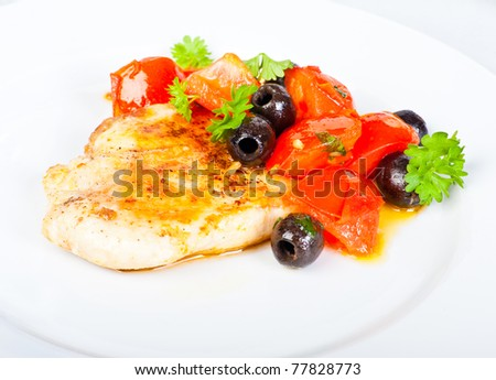 Chicken breast with tomato and black olives salad.