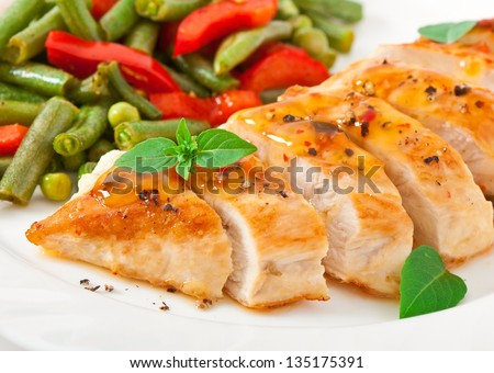 Chicken breast with vegetables and sauce decorated with basil leaves