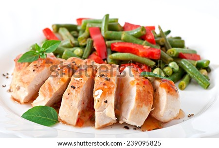 Chicken breast with vegetables and sauce decorated with basil leaves - stock photo