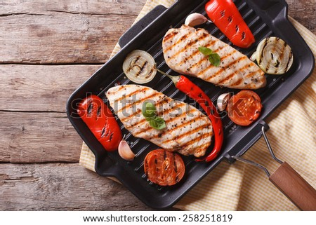 Chicken breast with vegetables and spices in a pan grill closeup. horizontal view from above
