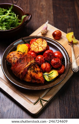 chicken breast wrapped in parma ham with cherry tomatoes, garlic and herbs - stock photo