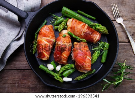 chicken breast wrapped in parma ham with green asparagus - stock photo