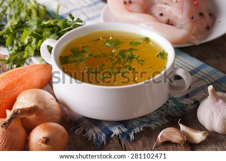 Chicken broth in a bowl and ingredients on the table close-up. Horizontal - stock photo