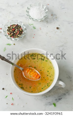 Chicken broth, salt, spices, dill on white marble background - stock photo