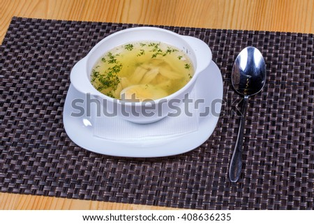 Chicken broth with a half cooked egg and greens  - stock photo