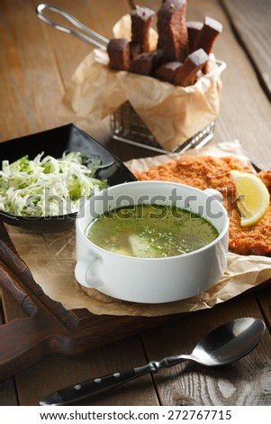 Chicken broth with egg, fried meat in batter, lemon and fresh salad on a brown wooden background - stock photo