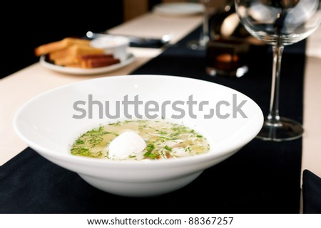 Chicken broth with homemade noodles, vegetables and poached egg - stock photo