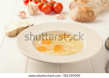 Chicken broth with noodles and carrots in a white plate on white wooden table. Shallow focus