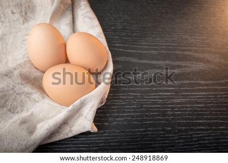 Chicken brown eggs in sackcloth on wooden background. - stock photo