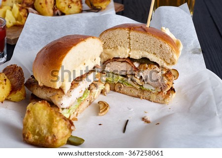 Chicken burger cut in two halfs with roasted potatoes and glass of beer in white paper for sanwiches on wood background - stock photo