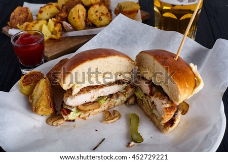 Chicken burger cuted in two halfs with roasted potatoes and glass of beer in white paper for sanwiches on wood background - stock photo
