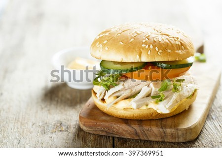 Chicken burger with cucumber and tomatoes - stock photo