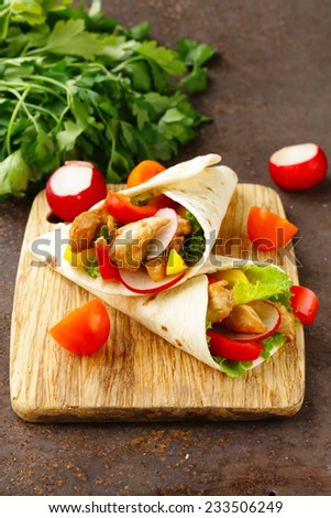 chicken burrito with radishes, sweet peppers and salad - stock photo