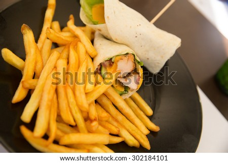 chicken burrito with sauce and French fries