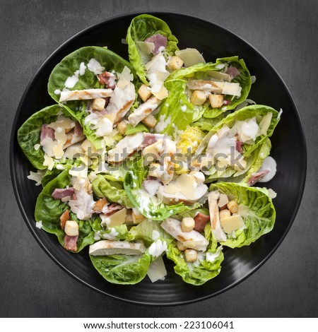 Chicken Caesar salad on black plate over slate.  Overhead view. - stock photo