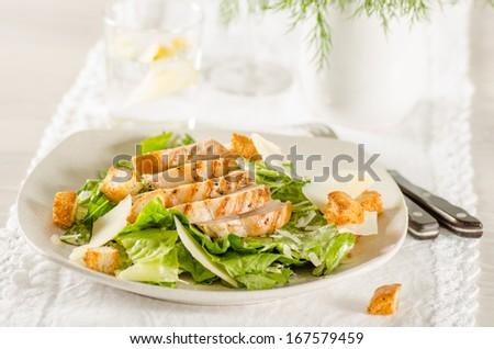 Chicken Caesar salad on the white plate - stock photo