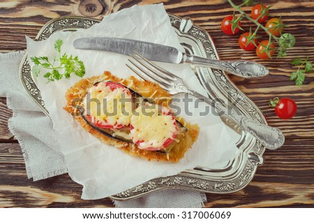 Chicken chop with tomato and eggplant under a cheese crust. Toned photo - stock photo